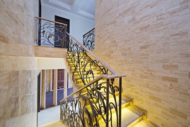 Лестница с подсветкой делает дизайн дома интересным и современным. Поручни лестницы из искусственного камня, ковка дополняет легкий дизайн лестницы.