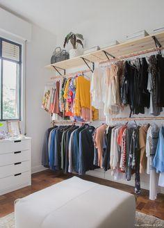 Closet DIY tem prateleiras de madeira crua e cabideiros feitos com canos de cobre e corda.