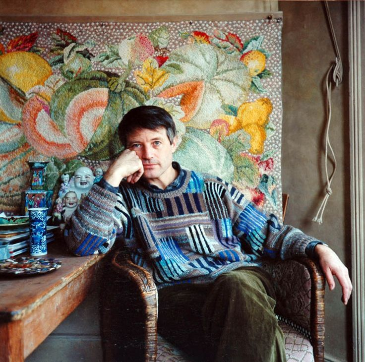 Young Colorist Kaffe Fassett in one of his own sweaters and in front of one of his needlepoint tapestries.