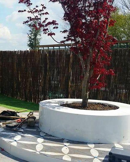 Dat is gezellig zitten rond de boom op deze aluminium boombank. Ook de kantopsluiting rond het tegelwerk is gemaakt van aluminium met een witte poedercoating in opdracht van Bouwman Buitenleven.
