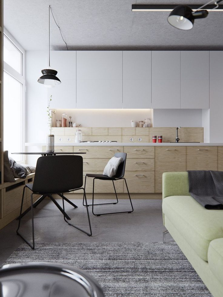 This 40sqm, two-level studio apartment plays with a cool background palette, allowing more unique-coloured furnishings to shine. Here, a wide avocado-hued sofa makes its mark on the main living area, while minimalist grey patterning and simple wooden textures give the room breathing space.