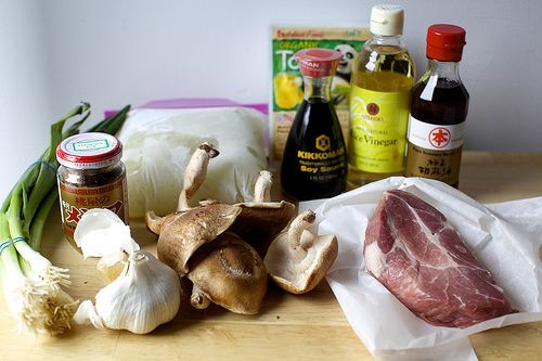 """1 oz (1/2 cup) dried wood ear mushrooms or 5 fresh button or shiitake mushrooms 2 T canola oil  1/2 lb lean pork shoulder, sliced 1-by-1/4"""" strips, or ground pork 1 T chopped garlic 1 T chopped peeled fresh ginger 1/2 C chopped scallions 4 C chicken stock  1/3 C (about 2 oz) bamboo shoots 1/2 Lb soft tofu, 1/2"""" dice 1/3 C rice vinegar, 3 T soy sauce 1 t sugar 1 t black or white pepper 1 t sesame oil 1 T Sriracha, plus more for serving Kosher salt 2 large beaten eggs"""