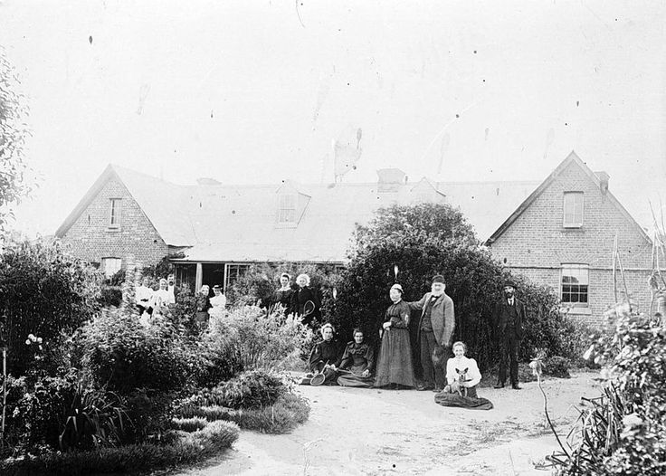 A group of people in the gardens at 'Pine Hills' homestead attending a tennis party, near Harrow, pre 1894.