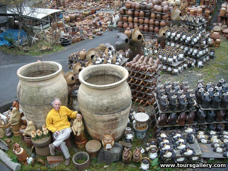 Ken Osetroff sits amongst pottery products in a kiln yard in Shigaraki Japan.