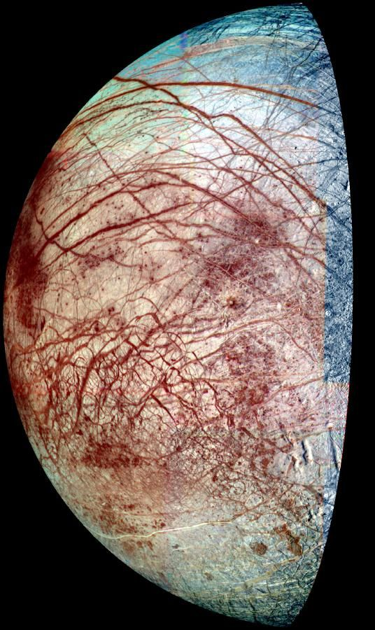 "The icy surface of Europa is shown strewn with cracks, ridges and ""chaotic terrain,"" where the surface has been disrupted and ice blocks have moved around."