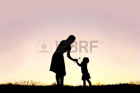 Een silhouet van een zoete peuter meisje overhandigt haar moeder een bloem van Daisy in een weiland  Stockfoto