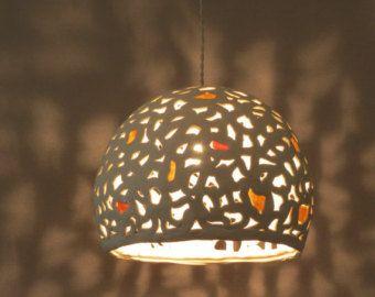 Deze keramische lamp schaduw is met de hand gemaakt van steengoed. Ik gebruik een techniek van breien de klei waardoor gaten waardoor het licht door te dringen. Dit maakt prachtige patronen van schaduwen op de muren en het plafond. Dit unieke hanger licht kan worden opgehangen boven uw eettafel of in een andere kamer.  U kunt zoveel lampenkappen als je zou willen en maak uw eigen kroonluchter. Voor een willekeurig aantal lampenkappen dan, neem contact met mij op voor de prijzen.  Lamp…