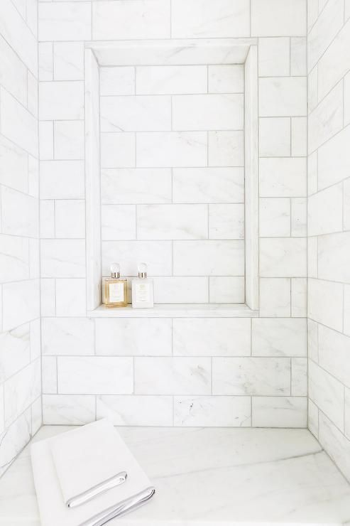 Chic walk in shower features honed white marble tiles fitted with a tiled niche shelf placed over a marble shower bench.