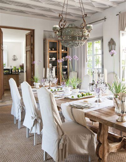 Roses and Rust. French country dining, natural wood farm table, loose linen chair covers