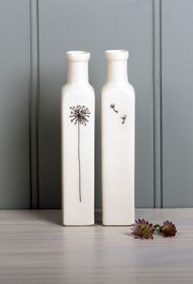A tall thin square sided porcelain bottle which lends itself to the dandelion illustration very well.   The dandelion head in on one side and the sees are on the back.  This image shows a lovely way of displaying two of the bottles together although they can be bought as a single bottle.