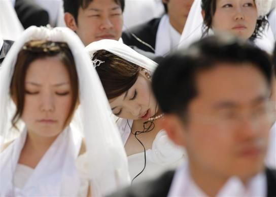 A bride takes a nap as newlyweds attend a mass wedding ceremony of the Unification Church at Sun Moon University in Asan, south of Seoul October 10, 2010. The Unification Church founded by evangelist reverend Moon Sun-myung in Seoul in 1954, performed its first mass wedding in 1961 with 33 couples. Seven thousand and two hundred couples attended the mass wedding. REUTERS-Lee Jae-Won