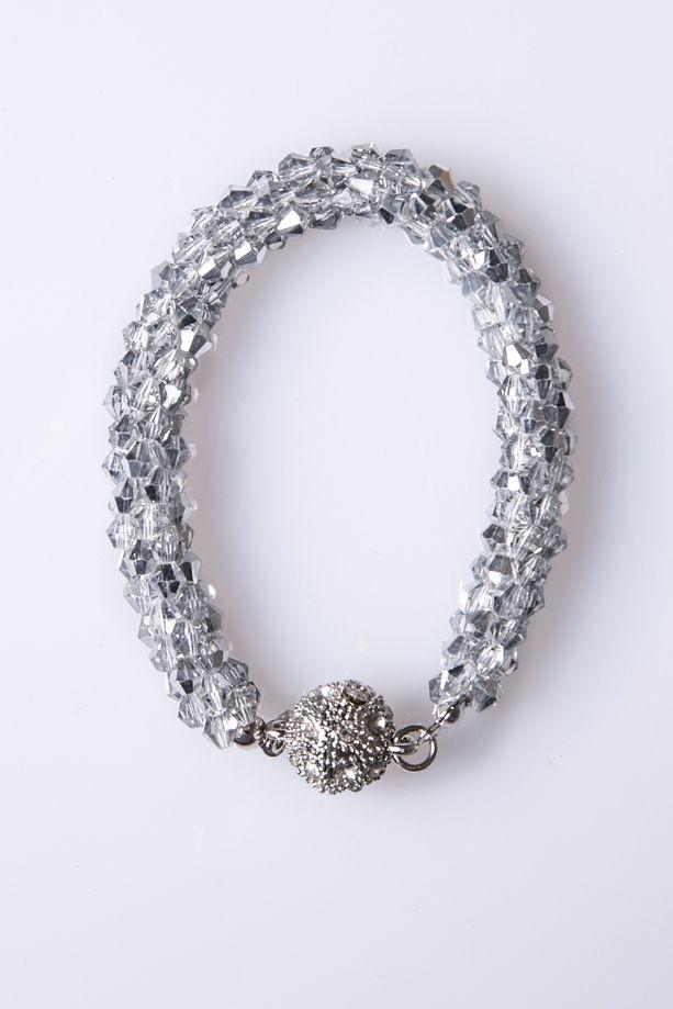 Bracciale realizzato da un intreccio di piccole pietre argentate sfaccettate, che riflettono la luce e risultano molto luminose. Chiusura magnetica a composta una sfera che si chiude a metà.  Dimensioni: 18 x 1 cm  #braccialetto #ecommerce #danishop #DANI #accessori #moda #donna
