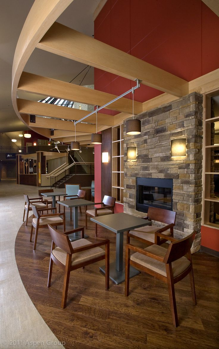 West Side Christian Church | Aspen Group flooring transition, track lighting exposed wood beam 'sofit.' Fireplace and warm colors