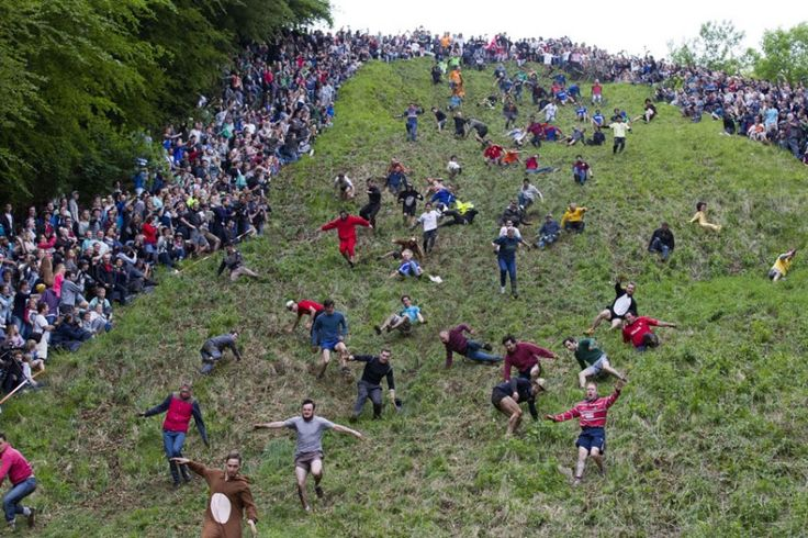 Competitors tumble down Coopers Hill in pursuit of a round double Gloucester cheese during the annual cheese rolling competition near the village of Brockworth near Gloucester...