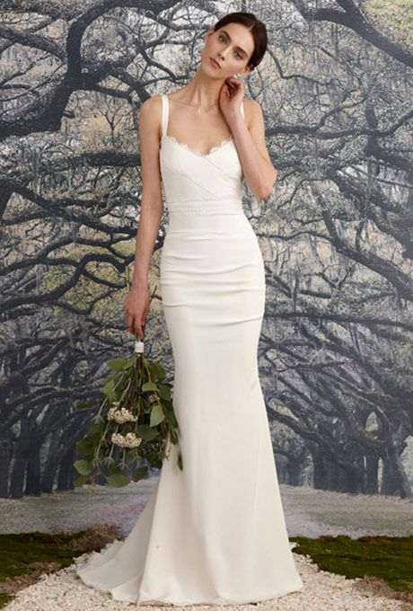 Brides: Nicole Miller. Mermaid gown center back and side ruching to slim and shape the figure. Faux-wrap V-neck bodice with scalloped lace detail. Classic shoulder straps lead into a deep V-back and fishtail train.
