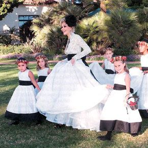 Shanna Moakler, in a lace Monique Lhuillier gown, walks with her flower girls after marrying Travis Barker.