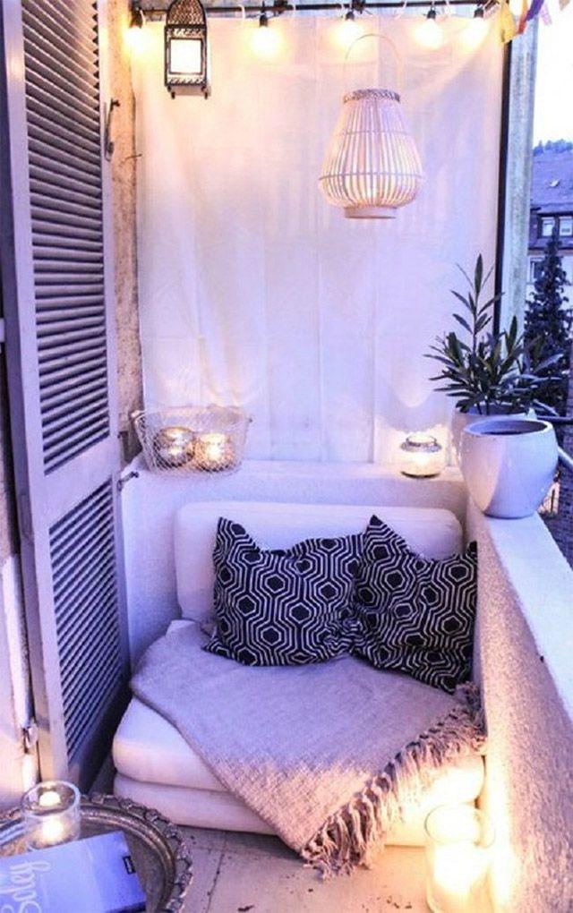Balcón pequeño en tonos blancos, silloncito al ancho del balcón con cojines blanco y negro y una manta, todo iluminado con fanales de vidrio puestos sobre el suelo, guirnalda de ampolletas en el techo y dos lámparas tipo farol.