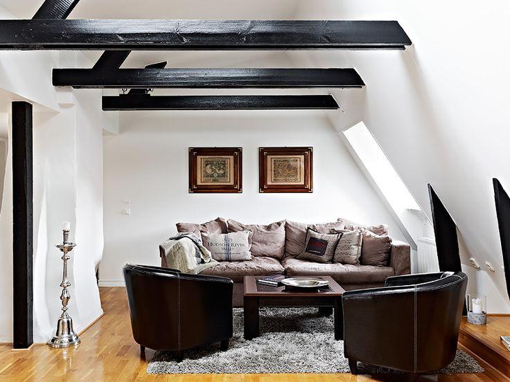 Contraste poutres et cuir noirs avec les murs blancs. Sofa invitant.   Un appartement sous les toits en Suède - Via Planète Déco