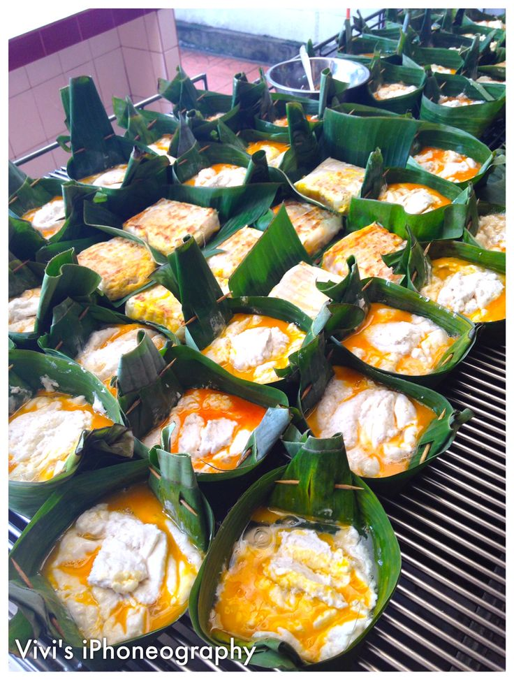 Pempek Bakar in Palembang, Indonesia. Pempek is uniquely Palembang trademark cuisine. It is a kind of fish cake. This one is cook on a grill and mix with eggs inside a pincuk (banana leaf folded as a bowl). Copyrights Vivi Kembang Tanjoeng.