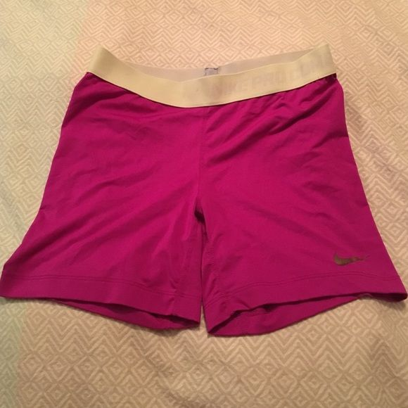 Nike Pro Magenta Compression Shorts Nike Pro combat Magenta Compression Shorts with fluorescent yellow waist band. Size medium. Front has one small spot and back has one thread out (seen in pic) Nike Shorts