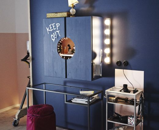 An image of a vanity station that consists of a cabinet, a small table and a place for the bathroom cart. The walls and cabinet are painted dark blue.