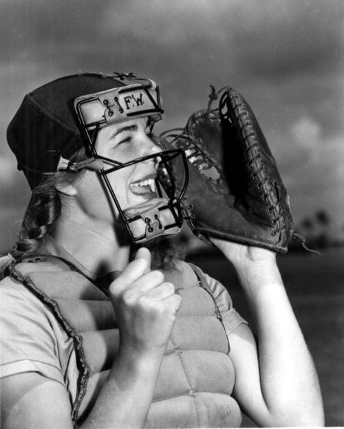 """Dottie Schroeder, catcher, shouting play ball behind mask. Photographed on April 22, 1948. Dorothy """"Dottie"""" Schroeder (1928-1996) was the youngest founding member of the All-American Girls Professional Baseball League at the age fifteen. After playing 12 seasons for the AAGPBL, she spent four years touring North America with an 11 woman team.  Her fifteen seasons of professional baseball remain a record for a female player."""
