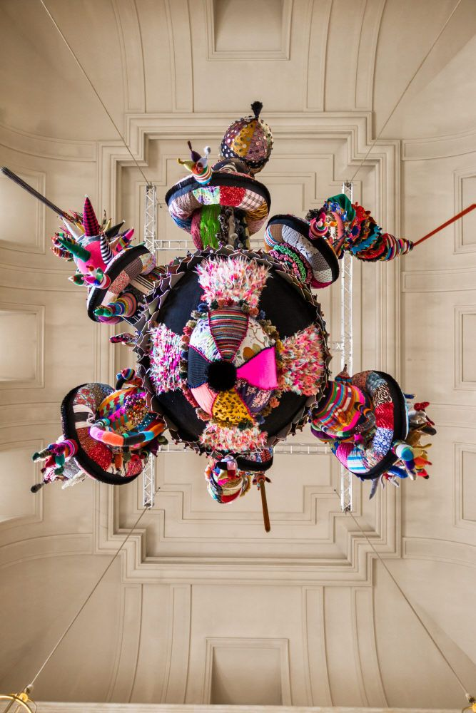 Mary Poppins, 2010  Artist +Source: Joana Vasconcelos  (view from below)    Handmade woollen knitting and crochet, industrial knitted fabric, fabrics, ornaments, polyester, steel cables700 x 600 x 600cmCollection of the artist    Crafted from the combination of pre-existing materials and mass-produced objects along with other hand-made crochet and knitted fabrics, Mary Poppins, gives continuity to the Valkyries series (started in 2004 with Valkyrie #1).