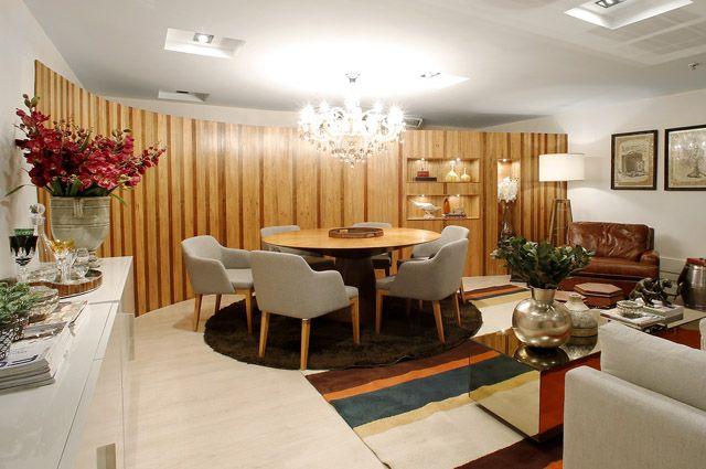 Mesa de jantar com tampo de madeira de reflorestamento e painel de madeira em parede curva com nichos dão destaque ao ambiente (Divulgação/S...
