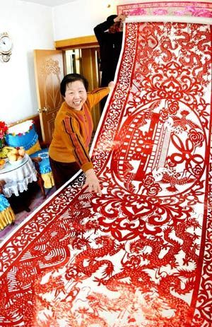 """Wang Yufen shows her papercutting """"100 Dragons Welcome the Beijing Olympic Games"""", in Shenyang, capital of northeast China's Liaoning Province, April 13, 2008. The 11-meter-long and 1.2-meter-wide papercutting includes the Olympic logos and 100 dragons in different patterns."""