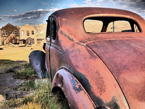 FINE ART PHOTO - I found this beautiful rusty vintage car half buried in the dirt in Bodie, a Ghost Town in California. Some of the old buildings are visible in the background.