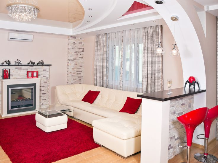 White living room with white sofa with red pillows and red rug