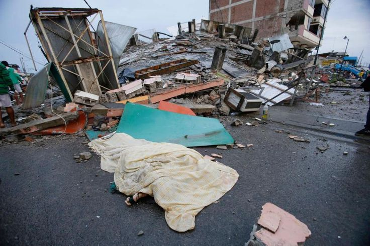 A body covered by sheet lies next to buildings destroyed by an earthquake in Pedernales, Ecuador, on April 17, 2016. The strongest earthquake to hit Ecuad