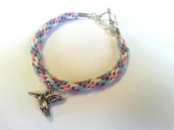 A handmade toggle bracelet of kumihimo bracelet in pastel colours (purple, blue, pink and white) with a choice of charm.