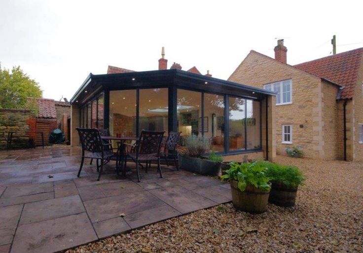 Modern glass extension on listed cottage