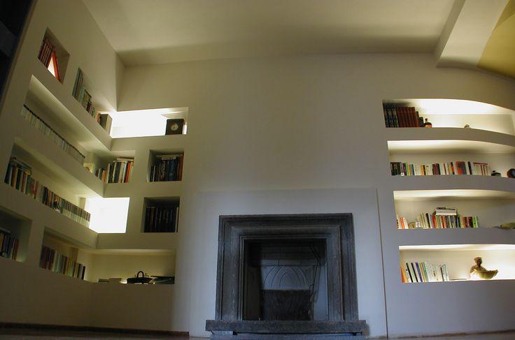 Camino in Peperino proveniente da Orvieto inserito in una parete-libreria in cartongesso Fireplace coming from Orvieto, realized in a wall-bookcase made of drywall