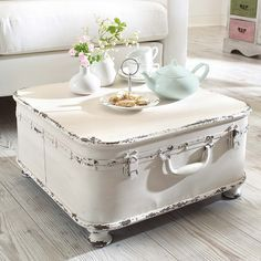 Shabby Chic.  I love It.  Take a suitcase or trunk, add feet... Voila, a coffee table! #whitedecor