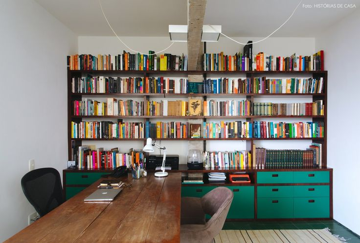 Home office com estante de madeira e fórmica verde e mesa de madeira rústica.