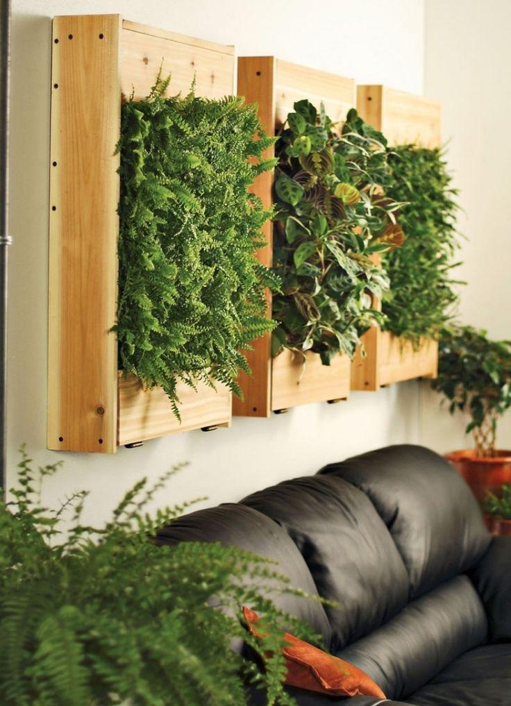 vertikaler-garten-wohnzimmer-ledercouch-schwarz-holzkonstruktion-farn-pflanzen-gruen
