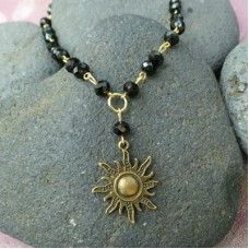 Sun Charm Necklace & Earring set, Black/Gold.  The sun is a constant staple that keeps life growing and evolving. The Sun is the star at the center of the solar system. It is by far the most important source of energy for life on Earth. Like our ancestors, we know the value of the sun and all that it provides us. For this reason the sun has been revered and Sun Gods and Goddesses. The sun represents energy, fertility, growth and happiness.  Necklace length: 48.5cm. Crystal beads. $26.00au