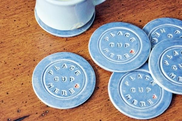 "Shop all of our clayware now!     Set of 4 ""Place Cup Here"" Coasters in Blue    PLACE CUP HERE coasters, hand made from stoneware clay, glazed in blue with red heart accent.   These coasters let your guests know to use a coaster on your nice furniture--without you having to tell them!"