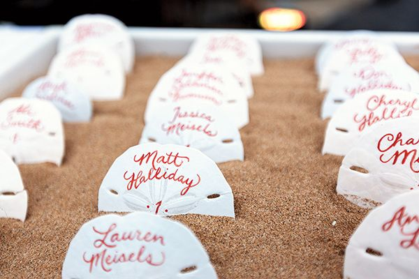 A destination wedding in Maui featured sandboxes containing sand dollar escort cards to tie in the couple's island theme.