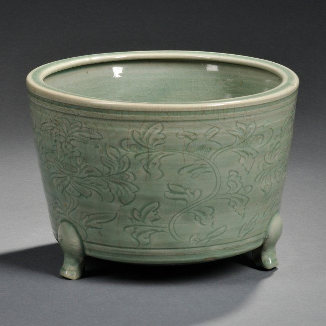 Tripod Celadon Censer, China, Ming Dynasty or later, the cylindrical body decorated with a floral pattern, supported by cabriole feet and a short foot ring, overall green glaze except at interior center and base, dia. 11 3/8 in.