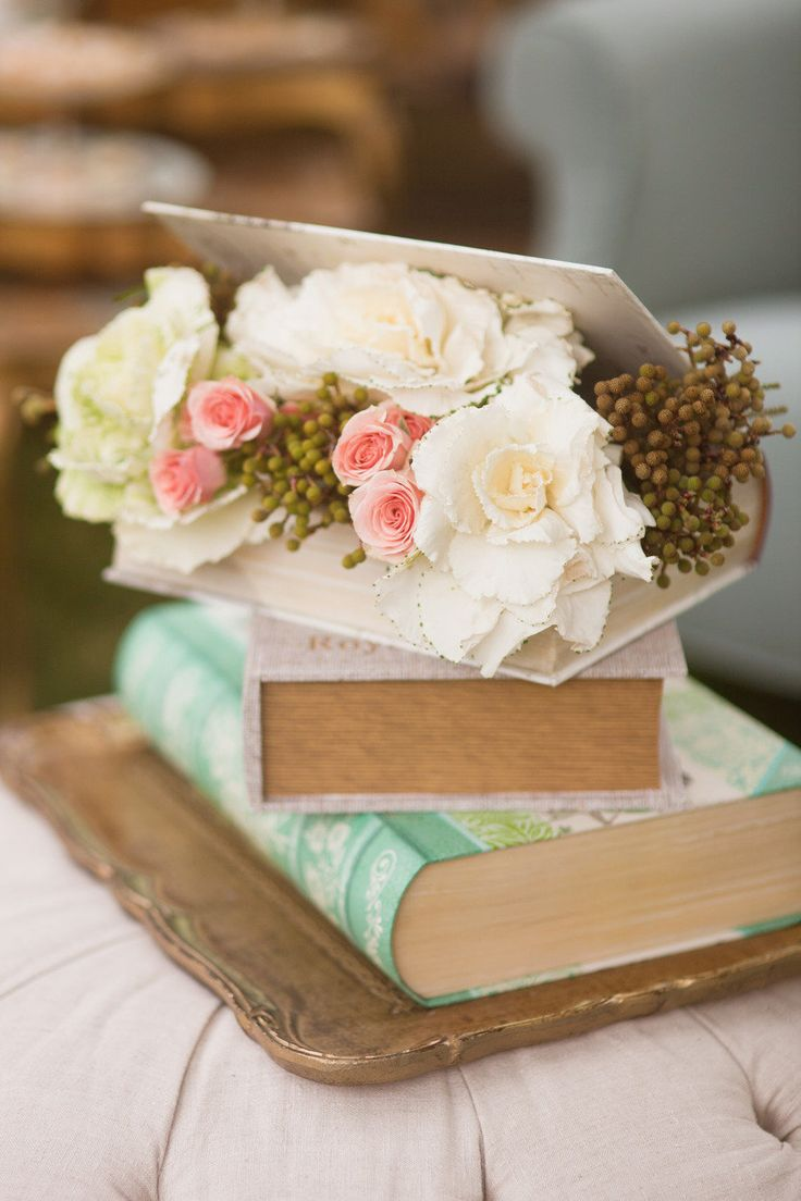 Use books you find at Goodwill, cover them with pretty paper, and arrange some flowers for a pretty display or centerpiece at a wedding or party.