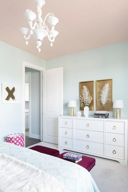 A pink ceiling beautifully complements light blue walls in this stylish girl's bedroom decorated with white and gold feather art pieces mounted above a white dresser accented with gold ring pulls and gold hammered lamps.