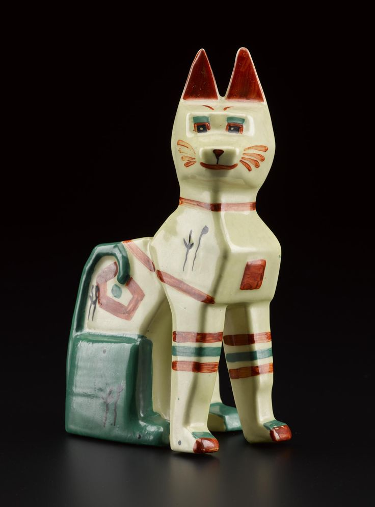 Ceramic spill vase in the form of an 'Egyptian' Futurist cat designed by Louis Wain and retailed by Max Emanuel & Co. Cream ground with painted facial features, stripes and abstract motifs in red and green, and black 'meow meow' notes. Main body signed 'Louis Wain' in black towards the bottom rear, printed makers marks and painted 'Rd No. 638318' on the base. English, c. 1914