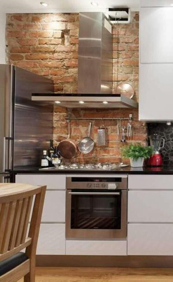 Vitt kök, svart marmor, tegel och borstat stål