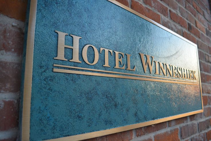 Bronze sign welcoming guest to the only full service hotel in Decorah Iowa