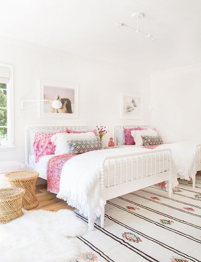 Modern girls' bedroom with twin iron beds, Moroccan rug, and pink patterned accents.