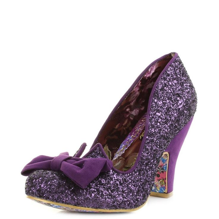 The Nick Of time from Irregular Choice is a quirky shoe from the brand the features a simple court shoe silhouette and block heel design that creates a easy wearing and comfortable shoe. The full purple glitter upper and suede style bow and heel makes this an eye catching and fun shoe perfect for making any outfit really stand out. This is a versatile shoe that will match many different events and parties and accompany many different styles. An ideal choice for bridesmaids and weddings too.