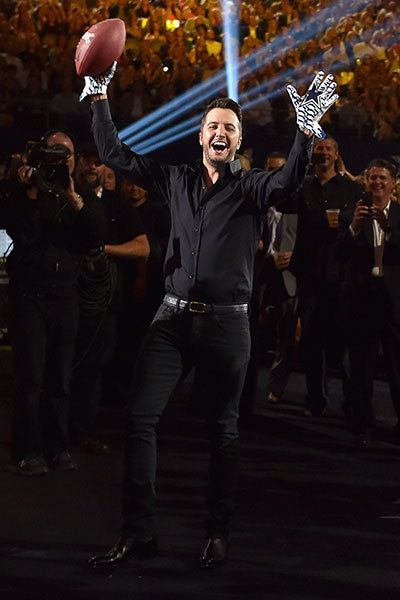 Luke Bryan catches a pass from Tony Romo at the 50th annual ACM Awards in Dallas on April 19, 2015.